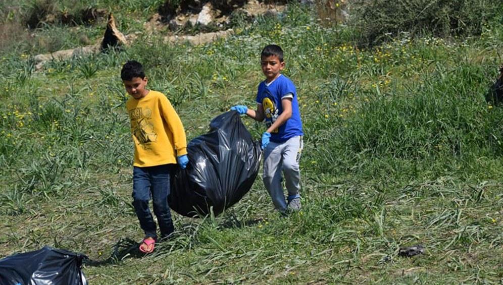Kinder räumen Müll weg